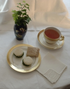 A Splendid Afternoon Teas with watercress rounds in the foreground and an English cucumber sandwich in the background.